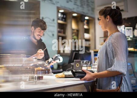 Barista calculating bill for female customer at cafe counter - Stock Photo