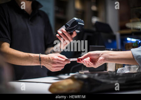 Close up of barista handing credit card to female customer - Stock Photo