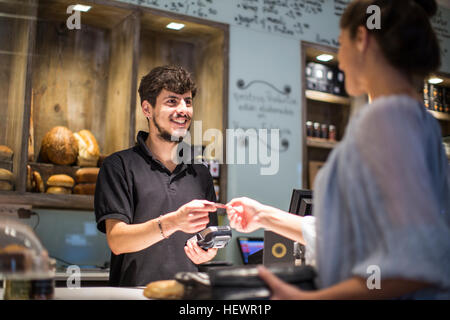 Barista handing credit card to female customer at cafe counter - Stock Photo