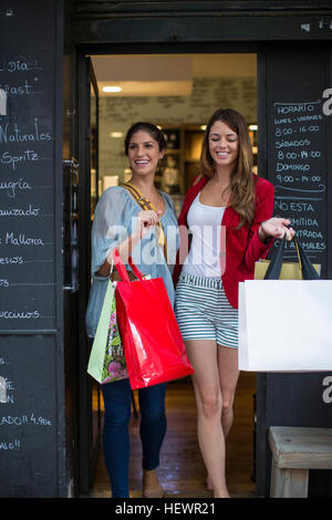 Two young female friends leaving cafe carrying shopping bags - Stock Photo