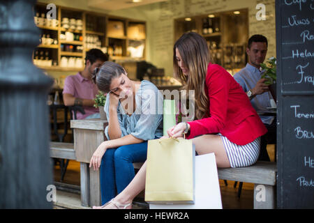Two young female friends with shopping bags chatting outside cafe - Stock Photo