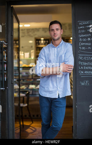 Portrait of mid adult male cafe owner leaning against cafe doorway - Stock Photo
