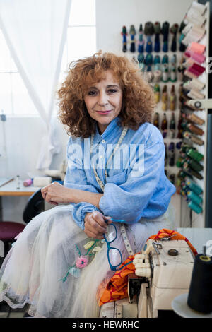 Portrait of woman in workshop looking at camera - Stock Photo