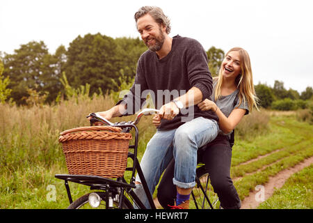Portrait of couple laughing whilst riding bicycle on rural dirt track - Stock Photo