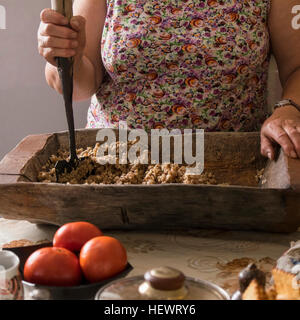 Cropped view of woman chopping food in wooden chopping board, Ural, Russia - Stock Photo