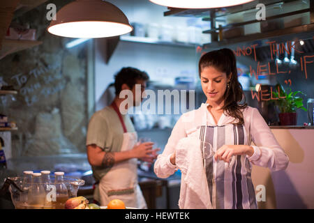 Restaurant owners working in kitchen - Stock Photo