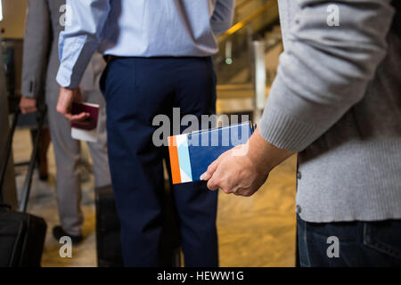 Mid section of passengers standing with boarding pass in queue in airport - Stock Photo