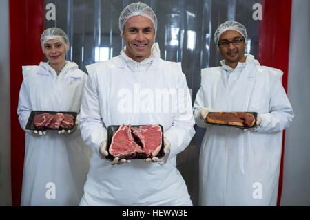 Portrait of butchers showing off meat trays at meat factory - Stock Photo