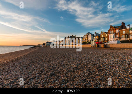 View along shingle beach with seafront promenade and town during sunrise over the sea. In distance, headland at - Stock Photo