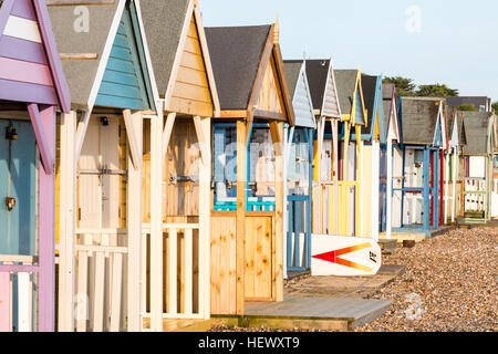View along Row of English traditional beach huts at Herne Bay on the Kent coast. Painted in various mainly pastel - Stock Photo