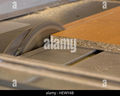 Circular saw cutting wood board. Workbench of carpenter, which prepares element for furniture building - Stock Photo
