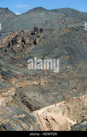 A 4WD descends a winding dirt road through a desert mountain pass. - Stock Photo