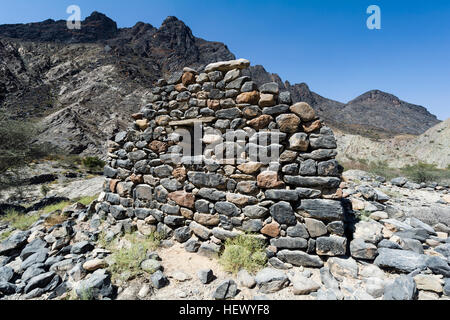 The ruins of a handmade stone house in an arid desert valley. - Stock Photo