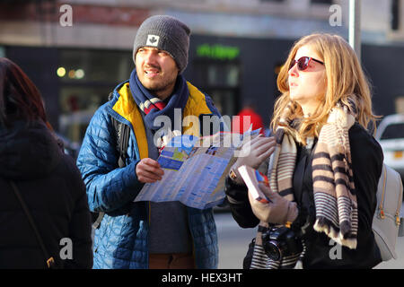 Two tourists with a map, guidebook, and camera look perplexed - Stock Photo
