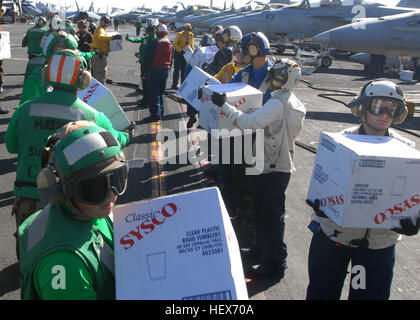 Sailors assigned to the aircraft carrier USS Ronald Reagan and embarked Carrier Air Wing 14 take boxes off of a - Stock Photo