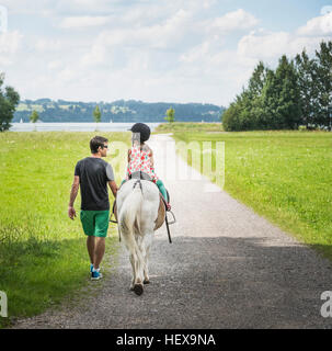 Rear view of father guiding daughter riding horse, Fuessen, Bavaria, Germany - Stock Photo