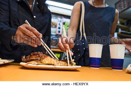 Two friends eating fish at the Nishiki street market in Kyoto, Japan - Stock Photo