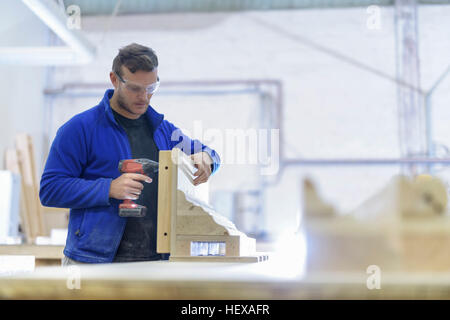 Carpenter making moulds in architectural stone factory - Stock Photo