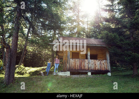 Two female friends leaving log cabin in forest, Sattelbergalm, Tyrol, Austria - Stock Photo