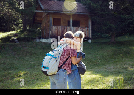 Two female friends hugging in forest glade, Sattelbergalm, Tyrol, Austria - Stock Photo