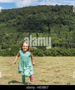 Girl running in field looking at camera smiling, Porta Westfalica, North Rhine Westphalia, Germany - Stock Photo