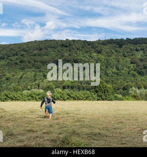 Rear view of boy running in field, Porta Westfalica, North Rhine Westphalia, Germany - Stock Photo