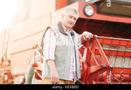 Portrait of farmer leaning against combine harvester looking away - Stock Photo