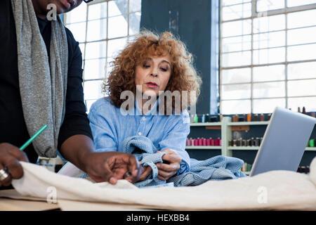 Male and female fashion designers examining material in design studio - Stock Photo