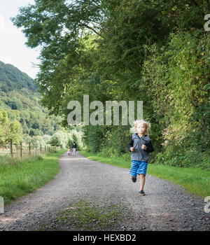 Boy with family running on rural road, Porta Westfalica, North Rhine Westphalia, Germany - Stock Photo