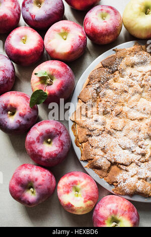 Apple pie with fresh Empire apples, overhead view - Stock Photo