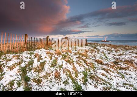 Sunset from the cliff top footpath looking towards St Mary's Lighthouse along a wooden fence in the snow, Whitley - Stock Photo