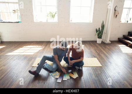 Young couple sitting on carpet in a loft looking at color samples - Stock Photo