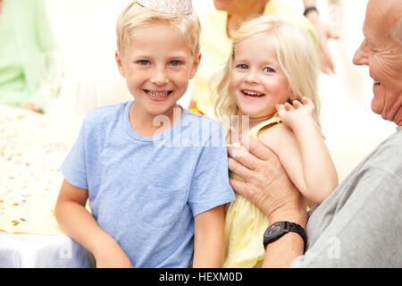 Blond boy and girl sitting on grandfather's lap - Stock Photo