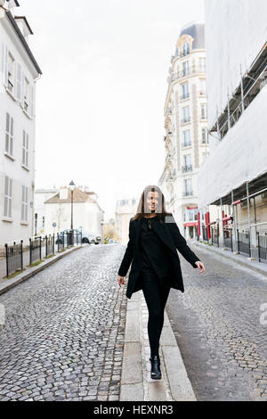 France, Paris, young woman walking on the streets of Montmartre - Stock Photo