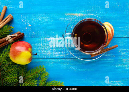 Winter warms festive Vitamin tea with apple and cinnamon on a blue wooden background in a transparent cup of glass. - Stock Photo