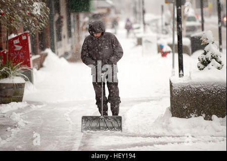 A man shovels snow of the sidewalk along Cleveland Avenue in Squamish BC, Canada during a snow storm blizzard. - Stock Photo