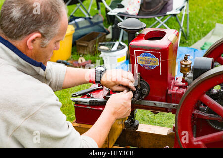 A man adjusts a Stationary Engine at a county show. - Stock Photo