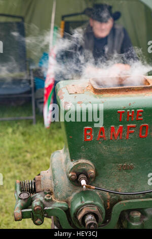 A close up of a Stationary Engine with steam coming out the top at a county show with the owner in the background. - Stock Photo