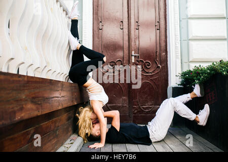 girl standing on the hands, a guy lying - Stock Photo