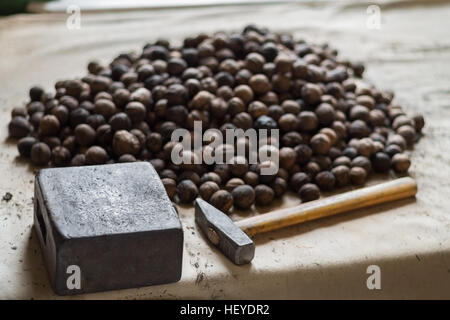 Whole walnuts on old table with anvil and nutcracker hammer - Stock Photo