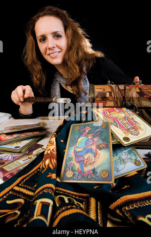 Fortune teller holding a wand over a magic box, a cloth decorated with the signs of the zodiac and tarot cards - Stock Photo