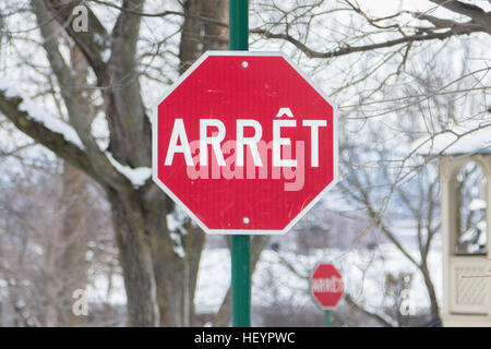 Stop sign (panneau arret) from Quebec in French in winter - Stock Photo
