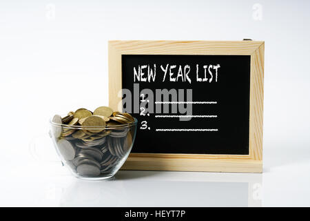 Coins in cup glass and blackboard with white text. New years concept. - Stock Photo