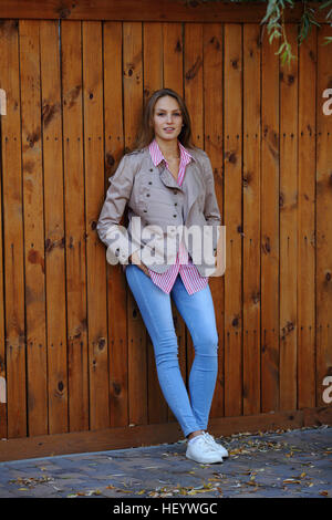 Young beautiful woman standing near wooden wall - Stock Photo