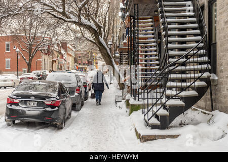 Montreal, CA - 17 December 2016: Snowstorm in Montreal. Pedestrian walking on a sidewalk. - Stock Photo