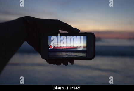 Hands holding mobile smart phone and take a video of the sunset in summer time - Stock Photo