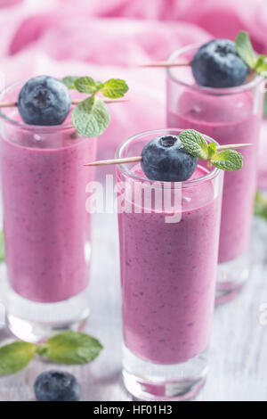 Delicious blueberry smoothie  with mint and fresh berries in glasses - Stock Photo