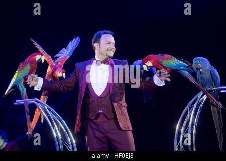 Animal trainer Alessio performs with parrots during the premiere of the Circus Krone winter program in Munich, Germany, - Stock Photo