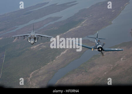 A Marine Corps AV-8B Harrier and vintage F4U Corsair fly side by side over the 2012 Marine Corps Air Station Cherry - Stock Photo