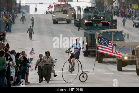 A parade performer weaves through vehicles of the Tennessee Army National Guard on his 1865 Penny farthing bike - Stock Photo